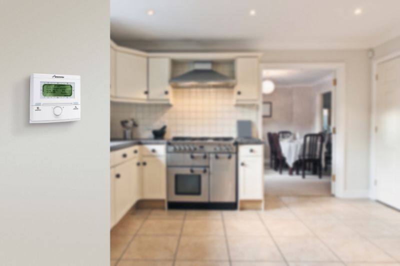 thermostat in focus with kitchen in background