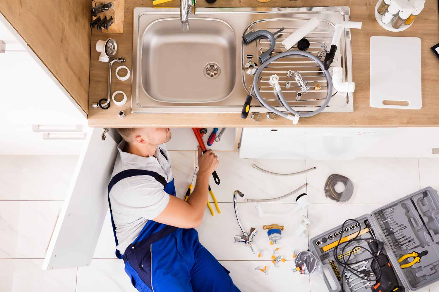 Plumber is fixing a burst pipe under a broken sink at a customer's home.