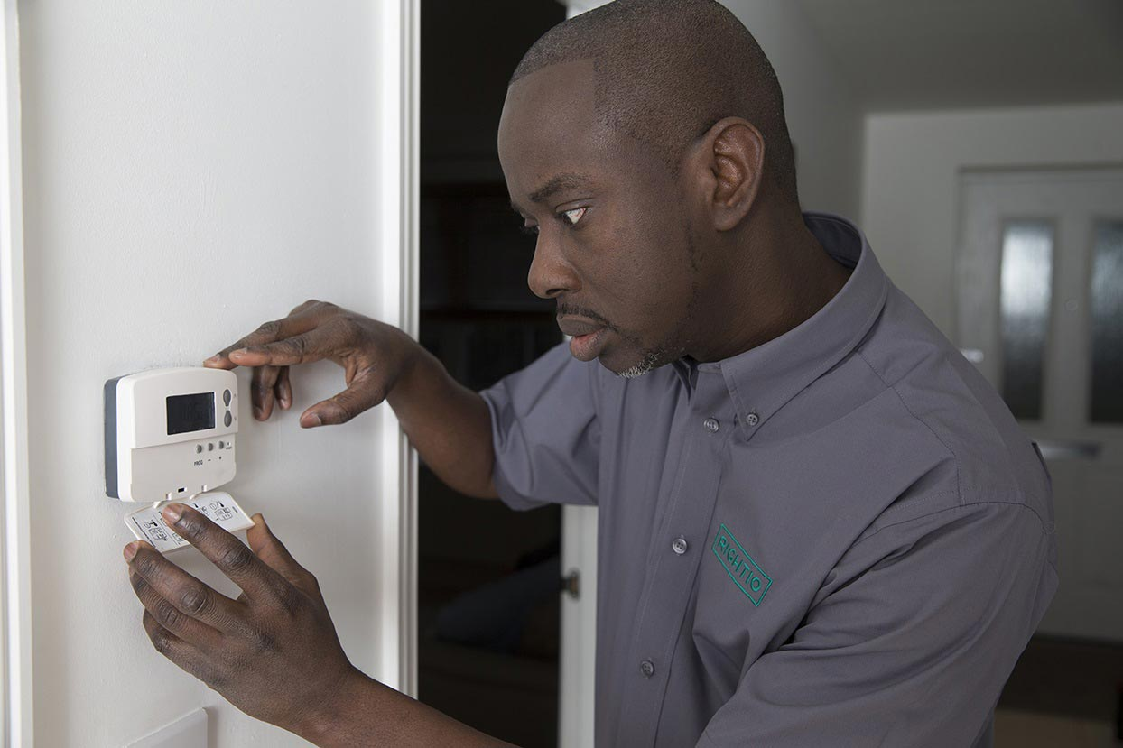 engineer inspecting thermostat