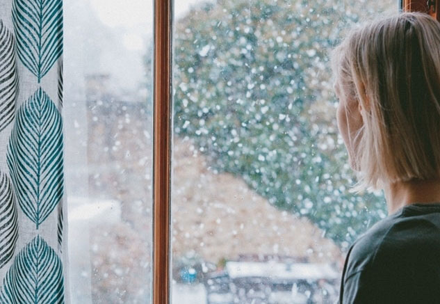 woman looking out window on snowy day