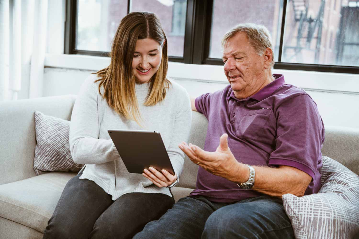 Daughter helping elderly vulnerable dad to stay in touch