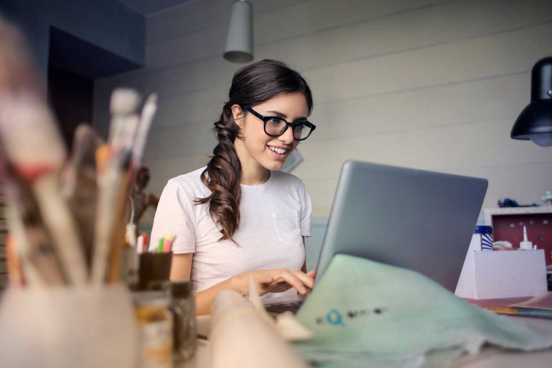 Woman working on laptop looking happy becuase of positive work-life balance in Birmingham